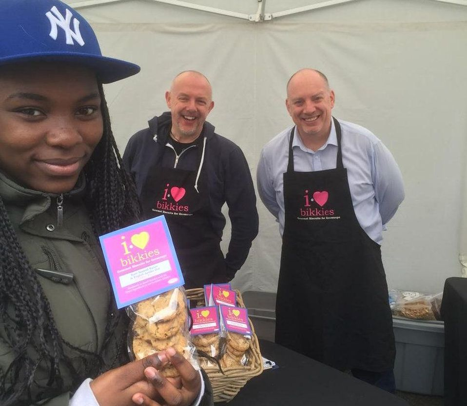 Young woman smiles after purchasing gourmet cookies from I Heart Bikkies at a market stall, with two owners