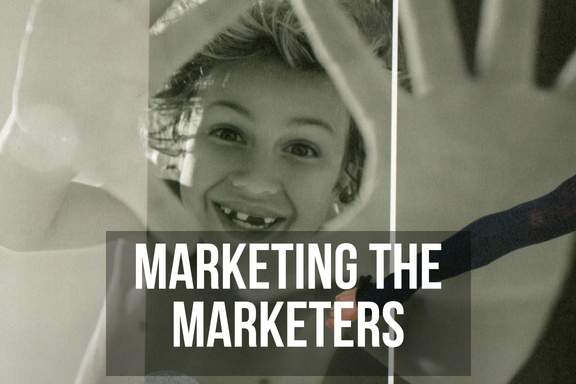 A small boy holds his hands up to the camera, with headline 'marketing the marketers'