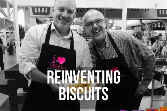 A pair of smiling men in aprons selling thier new cookies at a market with headline 'reinventing biscuits'